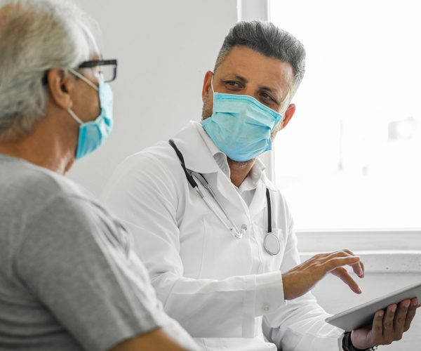 Doctor using digital tablet and talking to patient at home